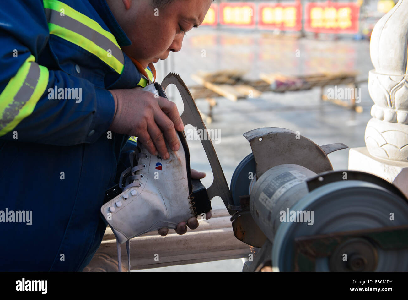Beijing, China. 10th Jan, 2015. A worker sharpens ice skate blade outside a skating rink at Shichahai, a scenic - Stock Image