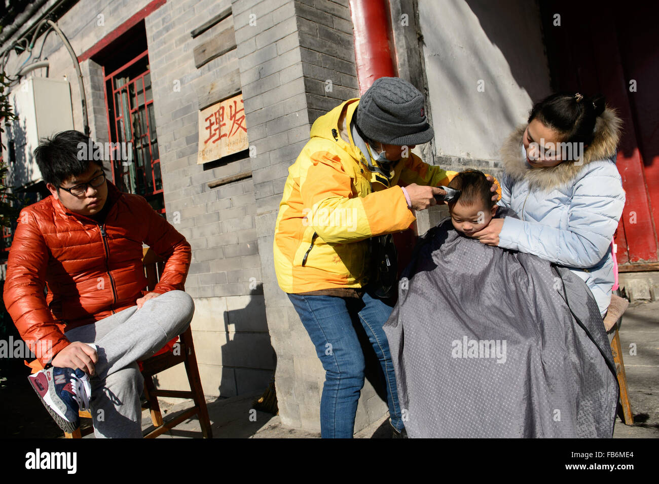 Beijing, China. 9th Jan, 2015. A child has hairs cut with parents at Shichahai, a scenic area in Beijing, capital Stock Photo