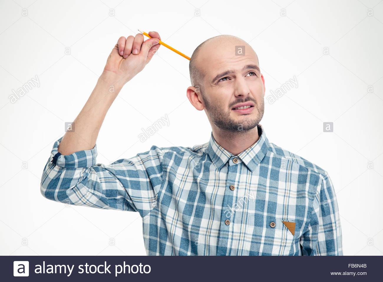 Thoughtful attrative young man scratching his head by pensil over white background - Stock Image