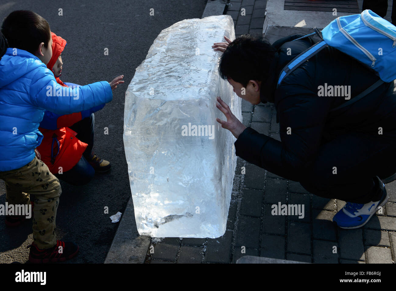 Beijing, China. 9th Jan, 2015. People watch an ice brick got from a lake at Shichahai, a scenic area in Beijing, - Stock Image