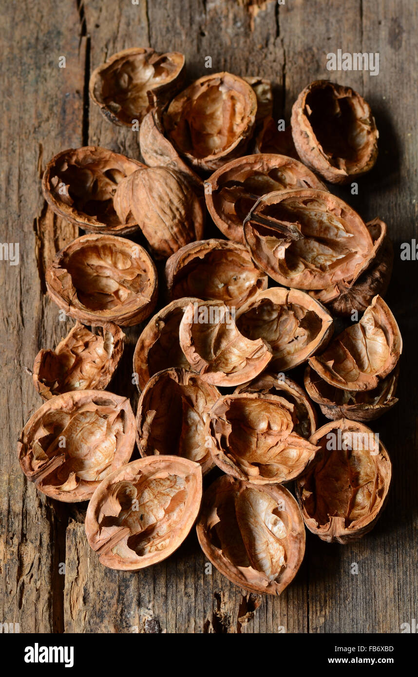 empty walnut shells on a rustic wooden table - Stock Image