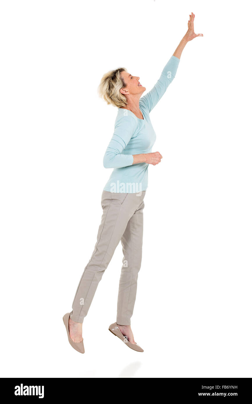 active senior woman jumping up and reaching out on white background - Stock Image