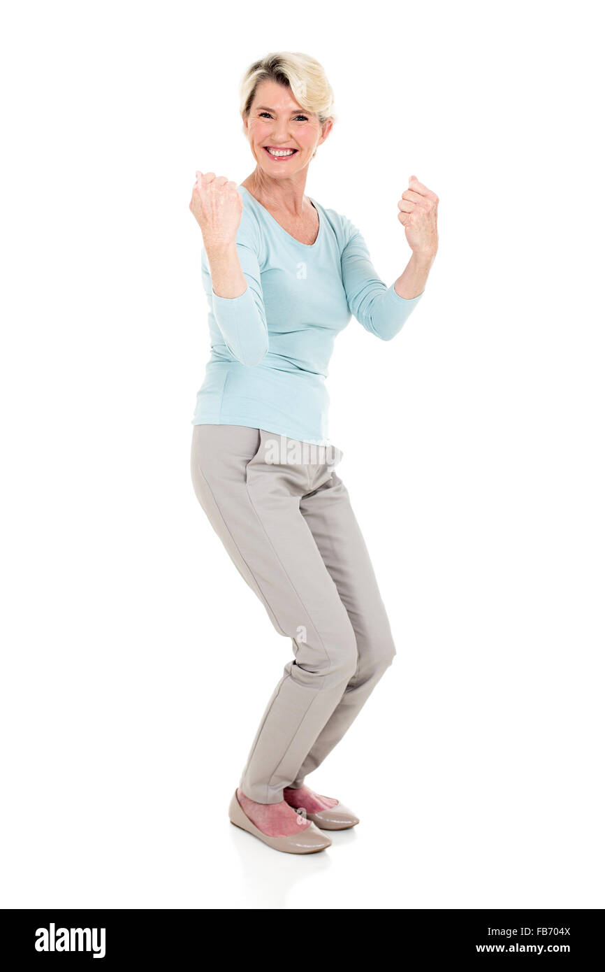 excited senior woman waving fists on white background - Stock Image