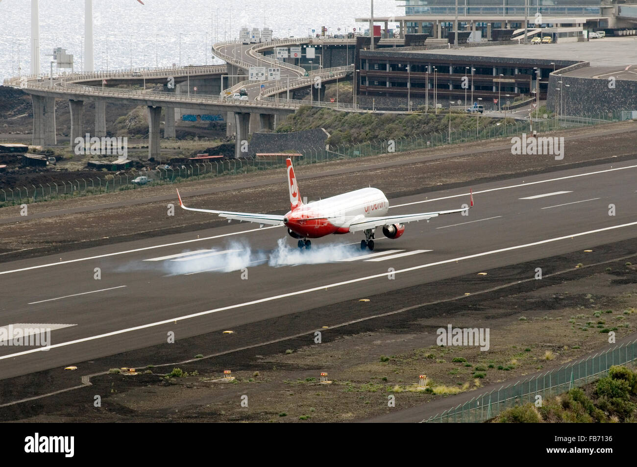 Air Berlin plane touching down at santa cruz la palma airport in the canary islands with smoke coming off the tires - Stock Image
