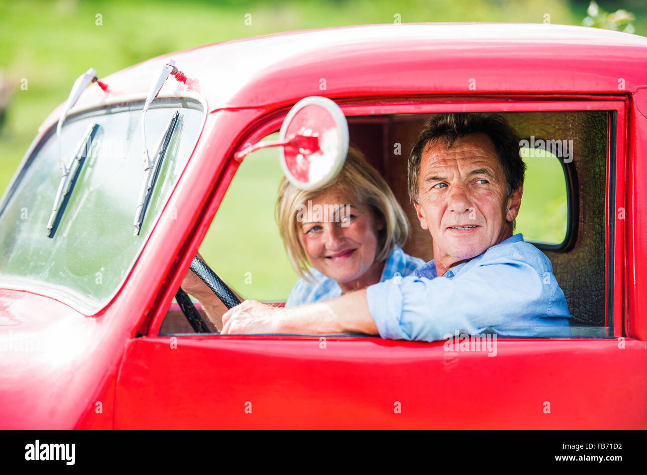 Senior couple in red car - Stock Image