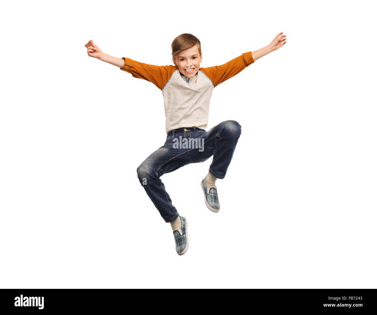 happy smiling boy jumping in air - Stock Image