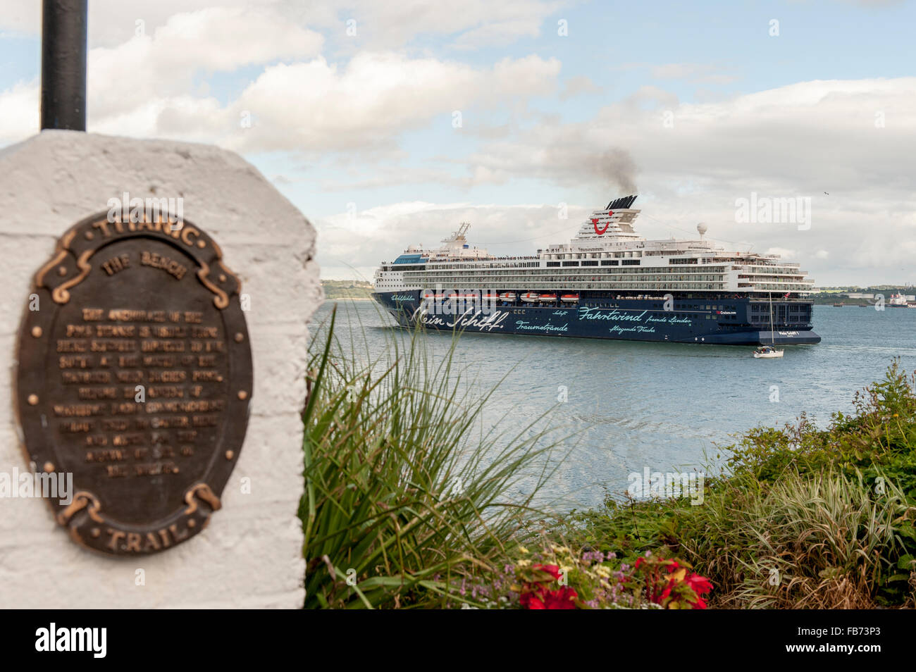 Luxury cruise liner Mein Schiff passes a Titanic Trail plaque as she sails from Cobh, Ireland on 27th July, 2015. - Stock Image