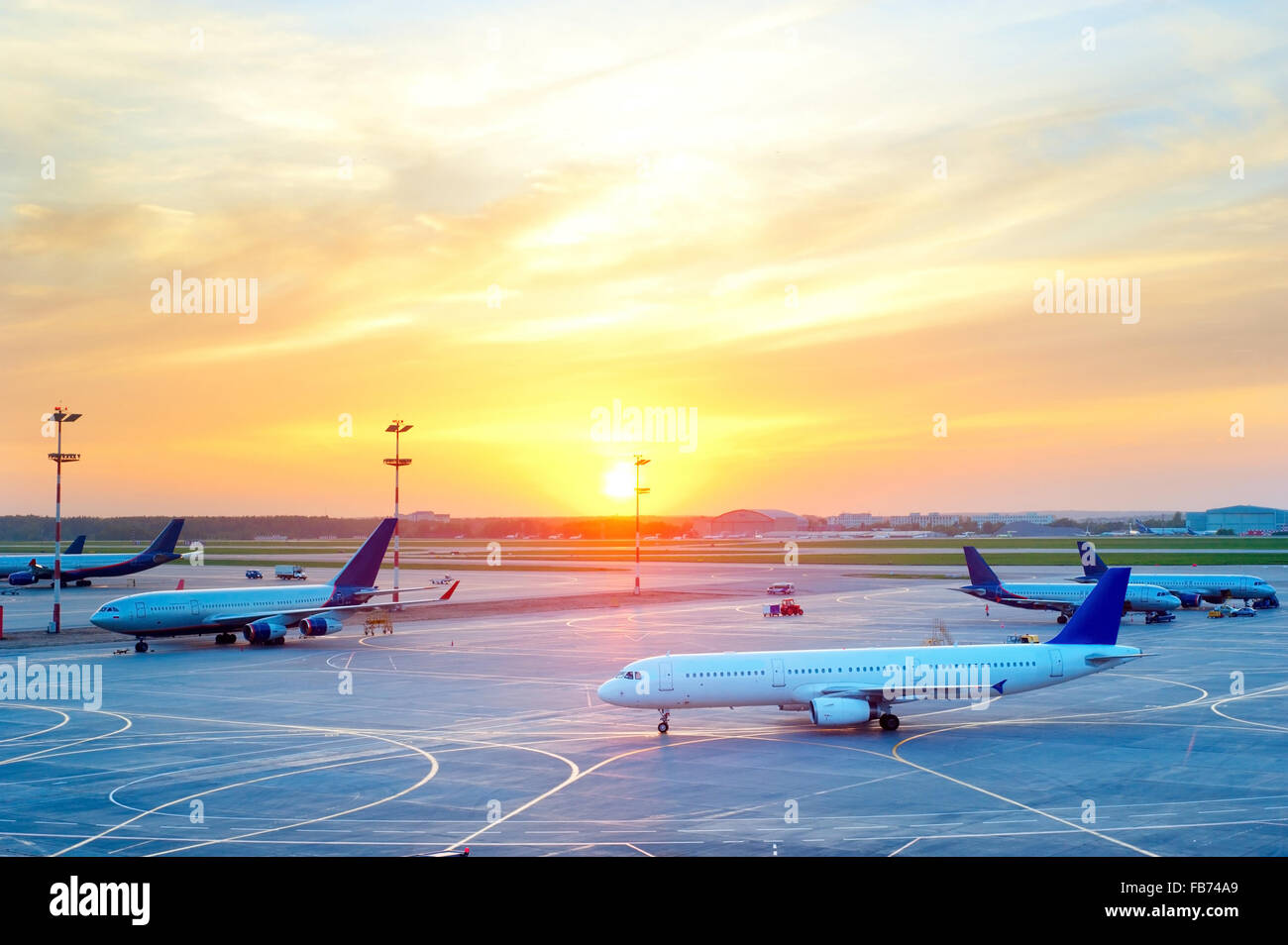 View of Airplanes at airport in the beautiful sunset - Stock Image
