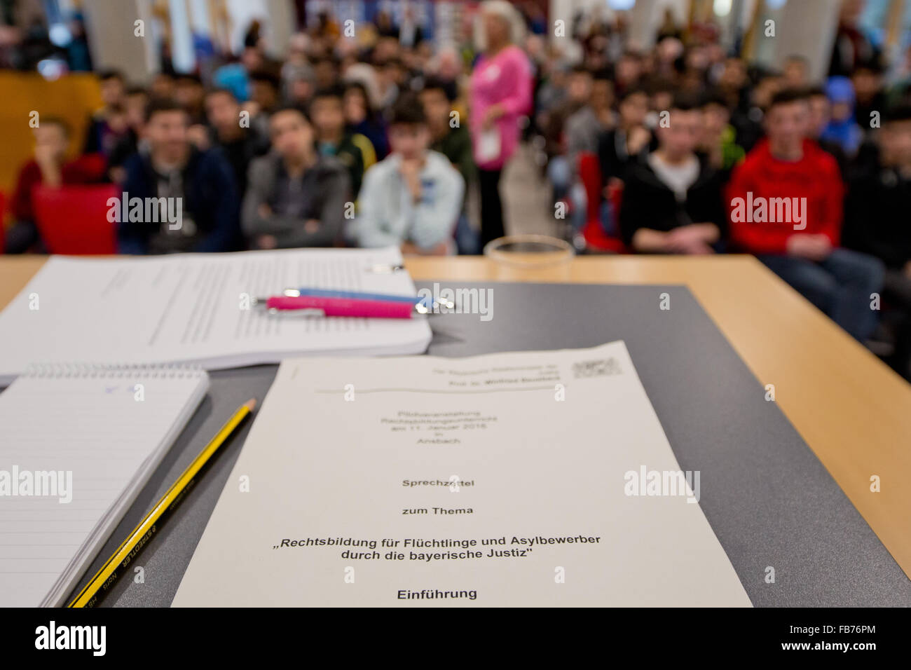 A document reads 'Legal education for refugees and asylum applicants through the Bavarian judiciary' during - Stock Image