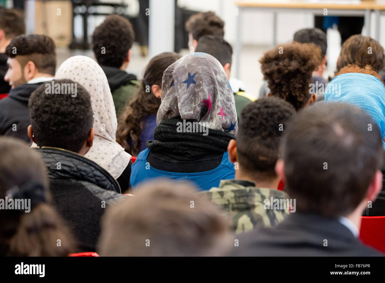 Refugees listen to a speech of the Bavarian interior minister during the launch of the project 'Legal education - Stock Image