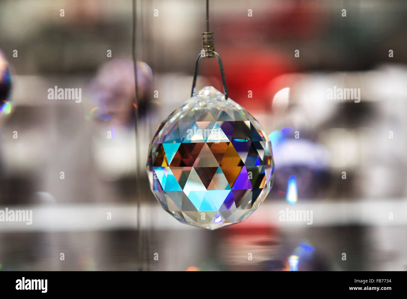 Faceted crystal hanging ball reflecting colorful light off the facets hanging on wire, close up with copy space - Stock Image
