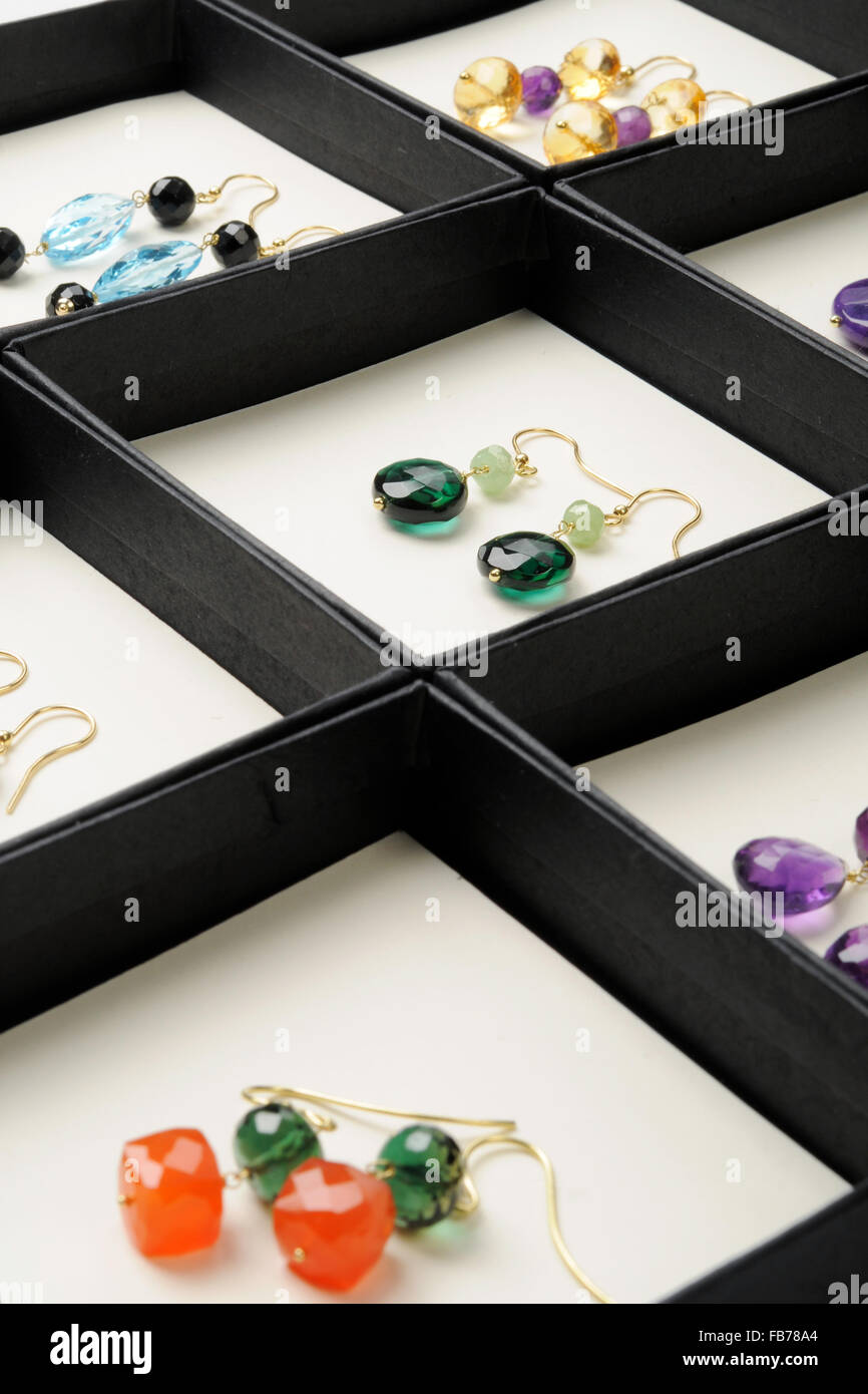 Display af handmade gemstone earrings with assorted cabochons and tumbled stones in amethyst, carnelian and assorted - Stock Image