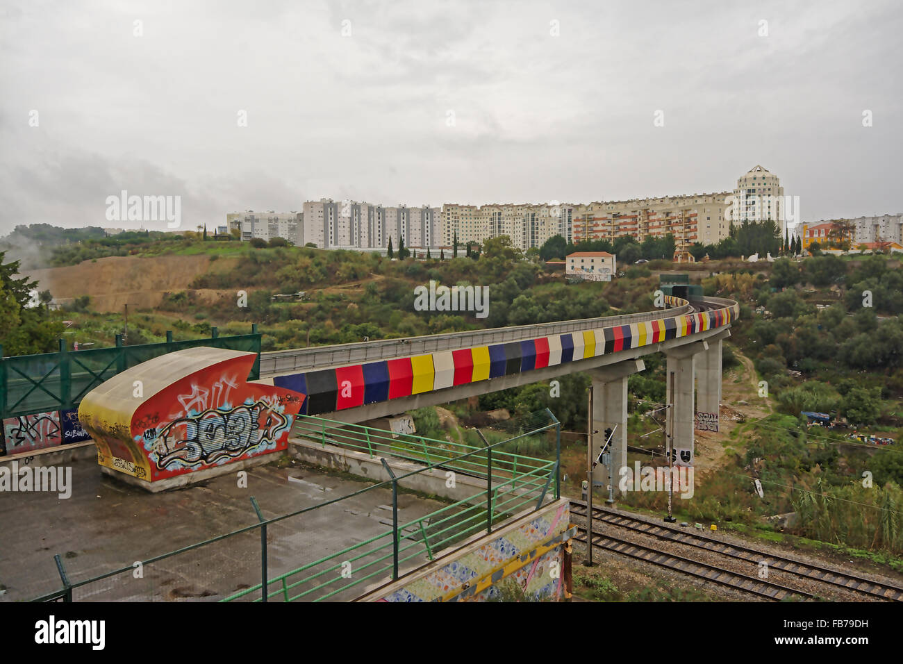 Colourfull train track with graffiti through urban wasteland with new apartment blocks in the background, lisbon, - Stock Image