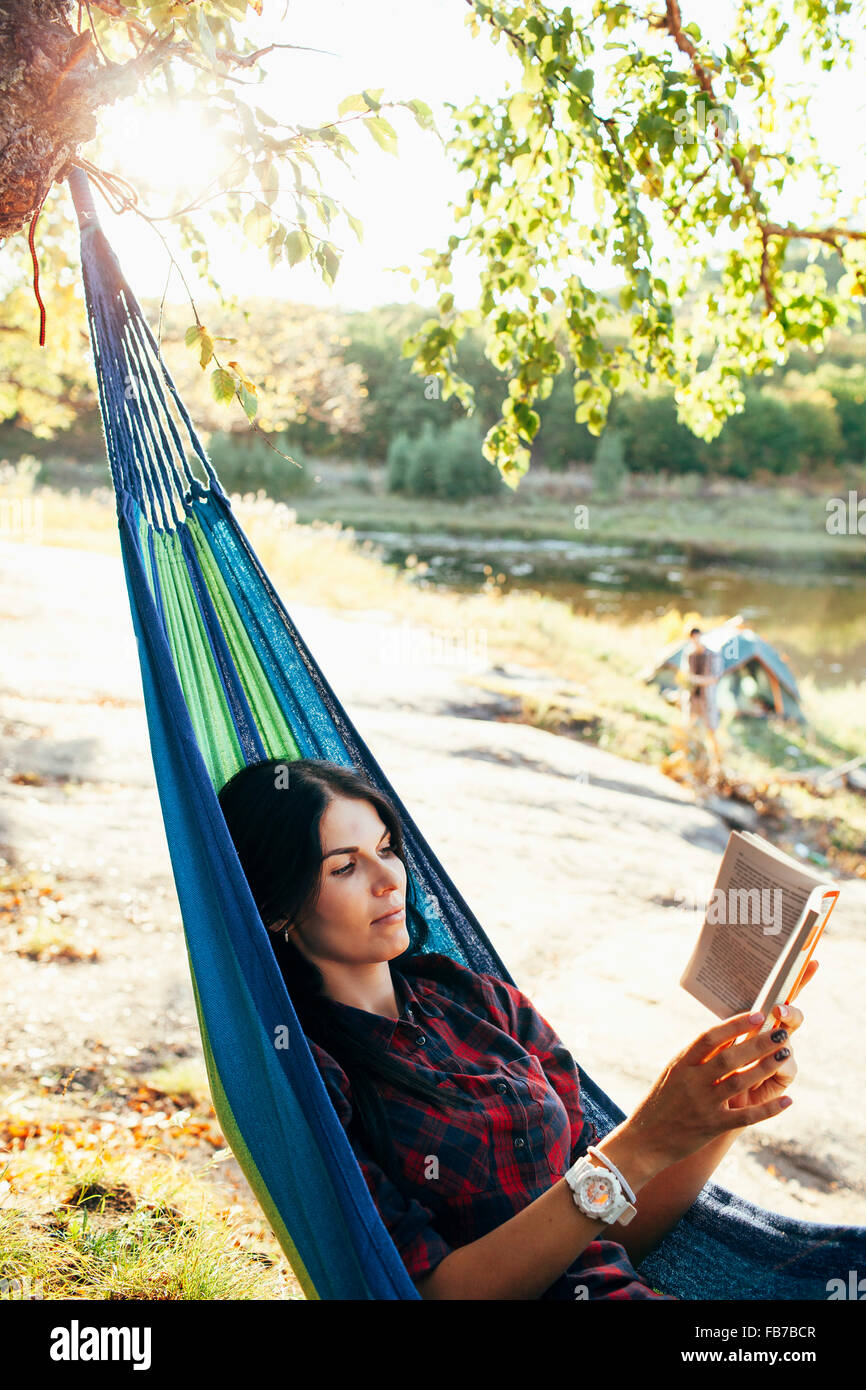 Young woman reading book while lying on hammock in forest - Stock Image