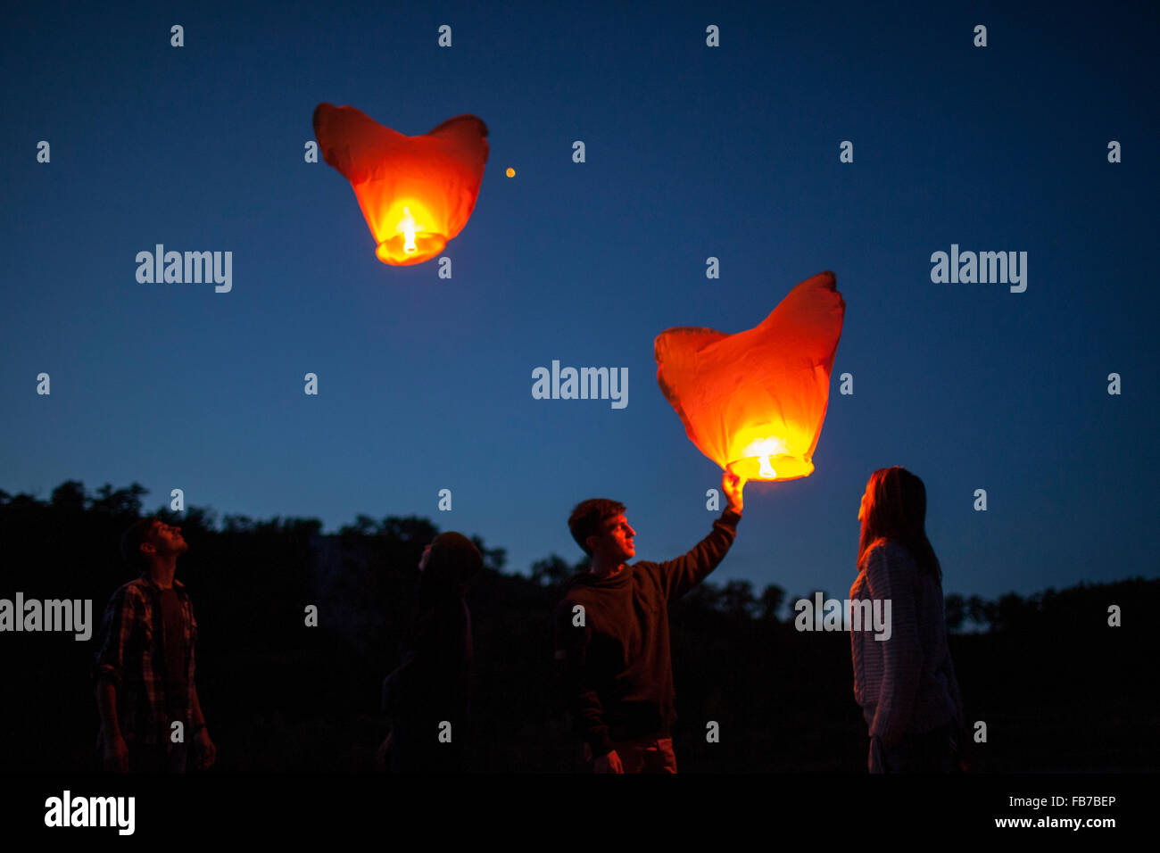 Low angle view of friends with paper lanterns in forest Stock Photo