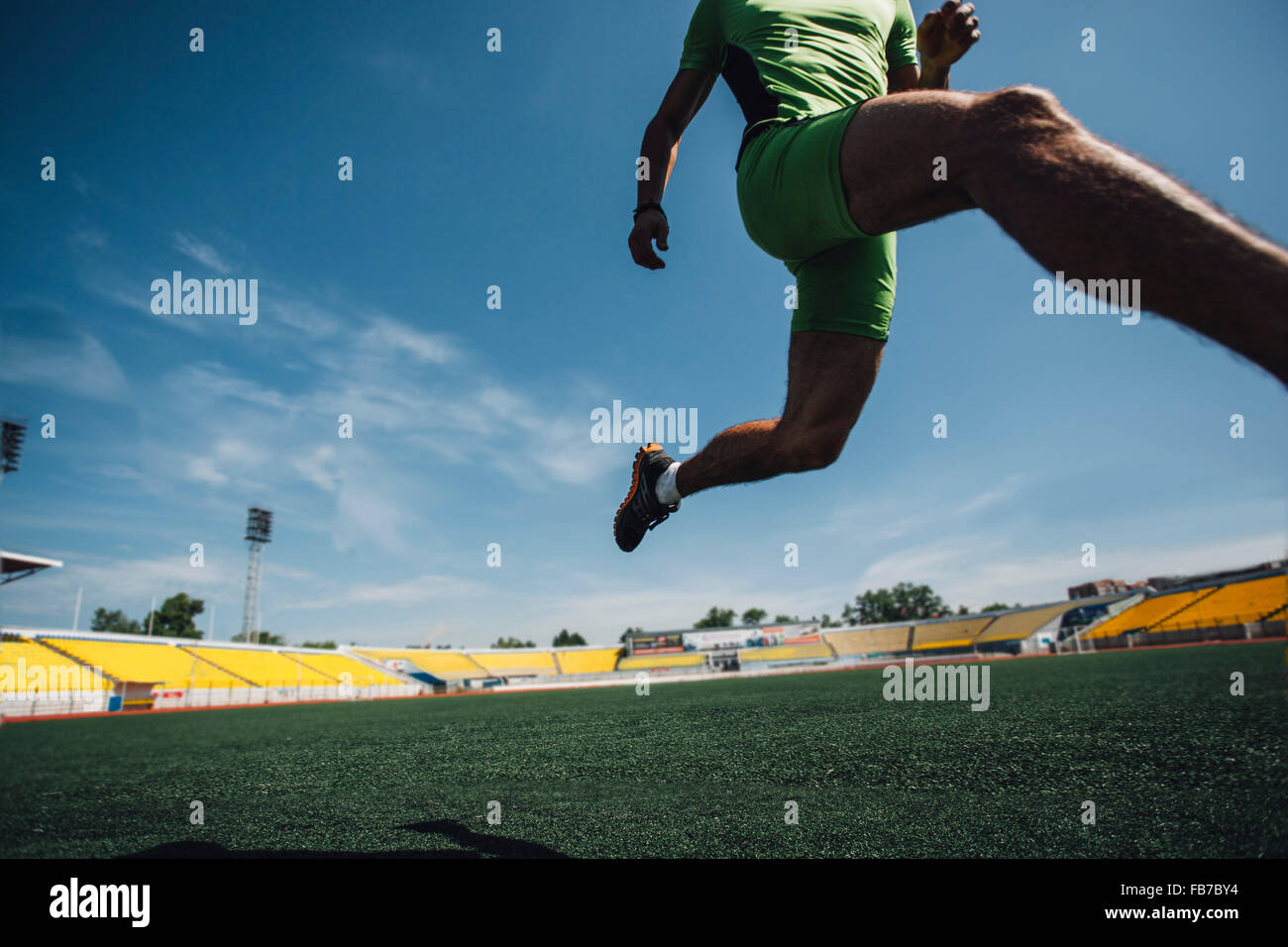 Low section of young male athlete running on field in stadium Stock Photo