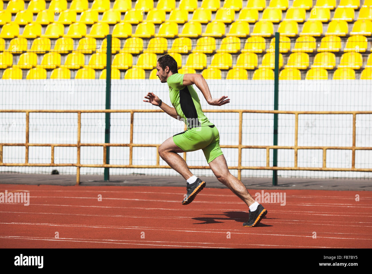Full length side view of sporty young man running on race track in stadium - Stock Image