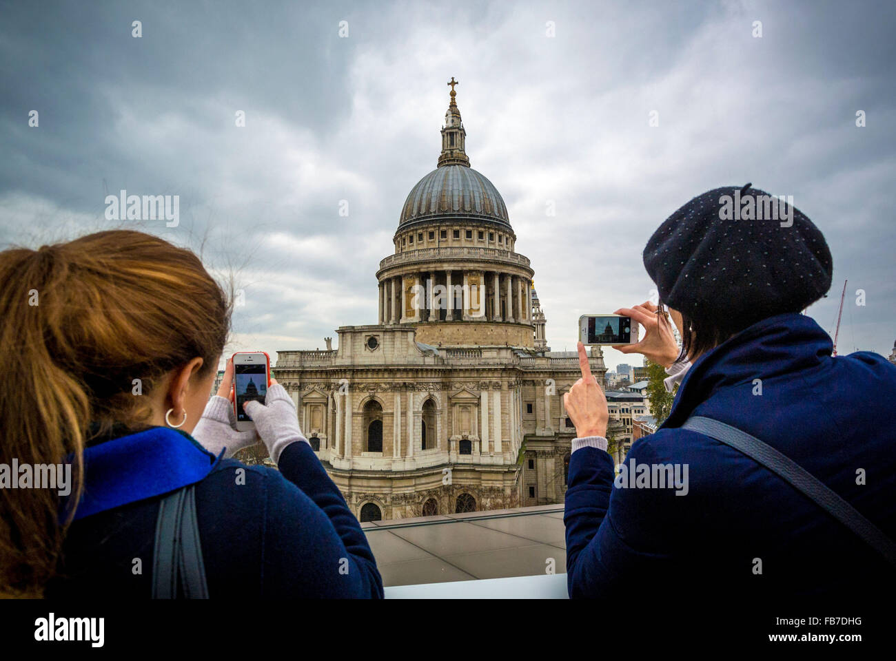 Two female tourists taking photos of St Paul's Cathedral on iphones - Stock Image