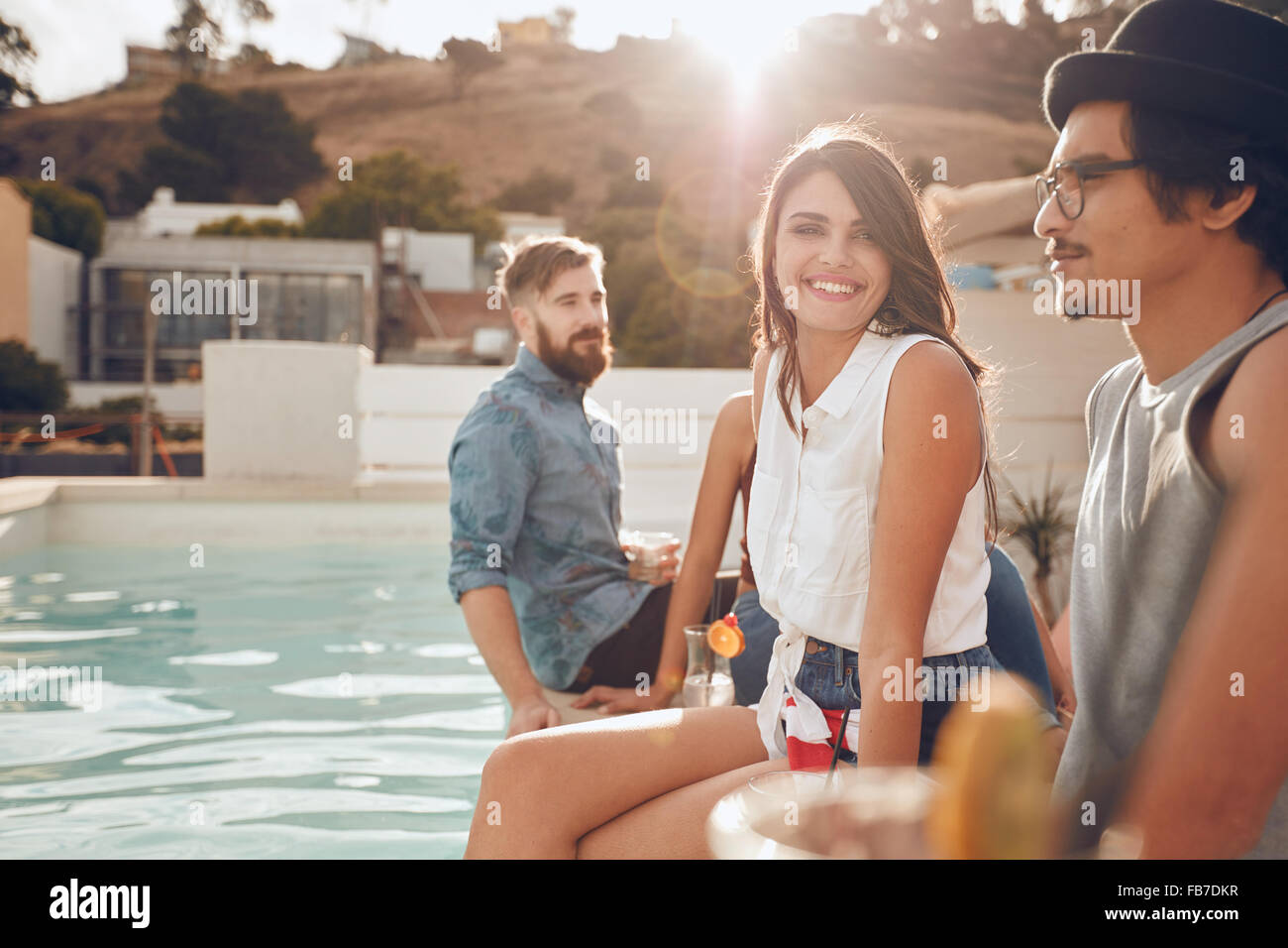 Portrait of beautiful young woman sitting by the pool with her friends around partying. Group of young people hanging - Stock Image
