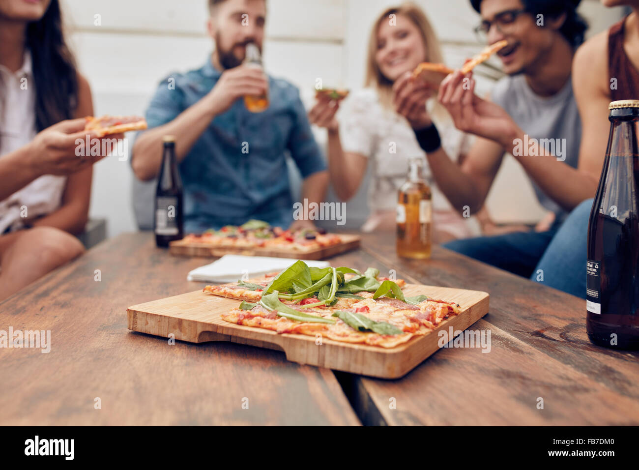 Close up shot of pizza on wooden plate with people eating and drinking in background. Group of friends gathered Stock Photo