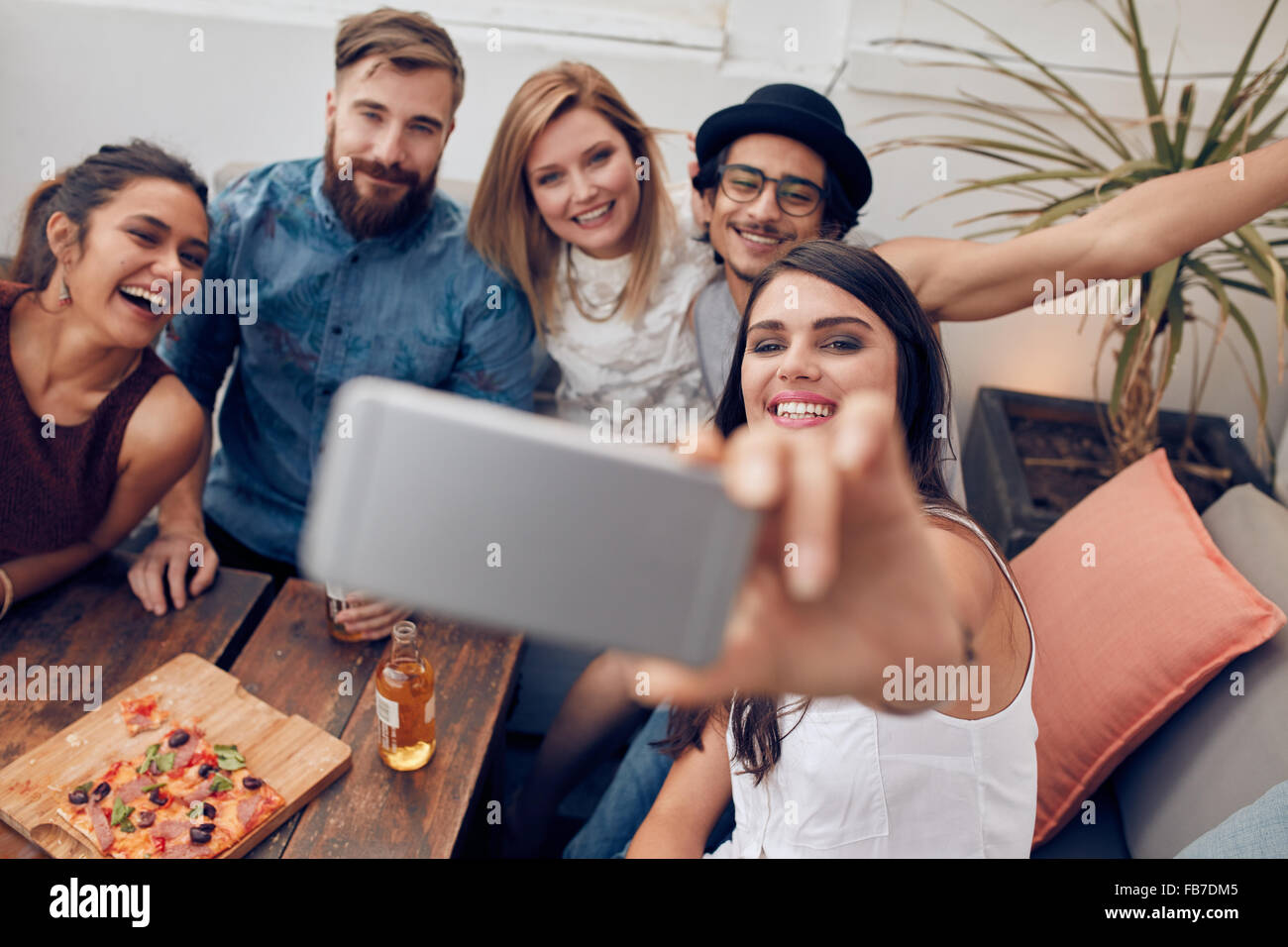 Multiracial people having fun at party taking a selfie with mobile phone. Group of young friends sitting on couch Stock Photo