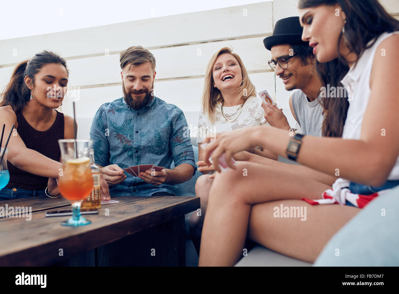 Group of friends sitting at a wooden table and playing cards. Cheerful young people partying together and playing - Stock Image