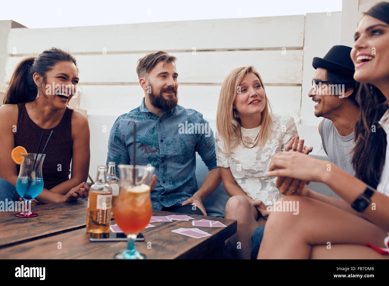 Group of friends relaxing together around a table. Young people hanging out around a table during a party with cocktails - Stock Image