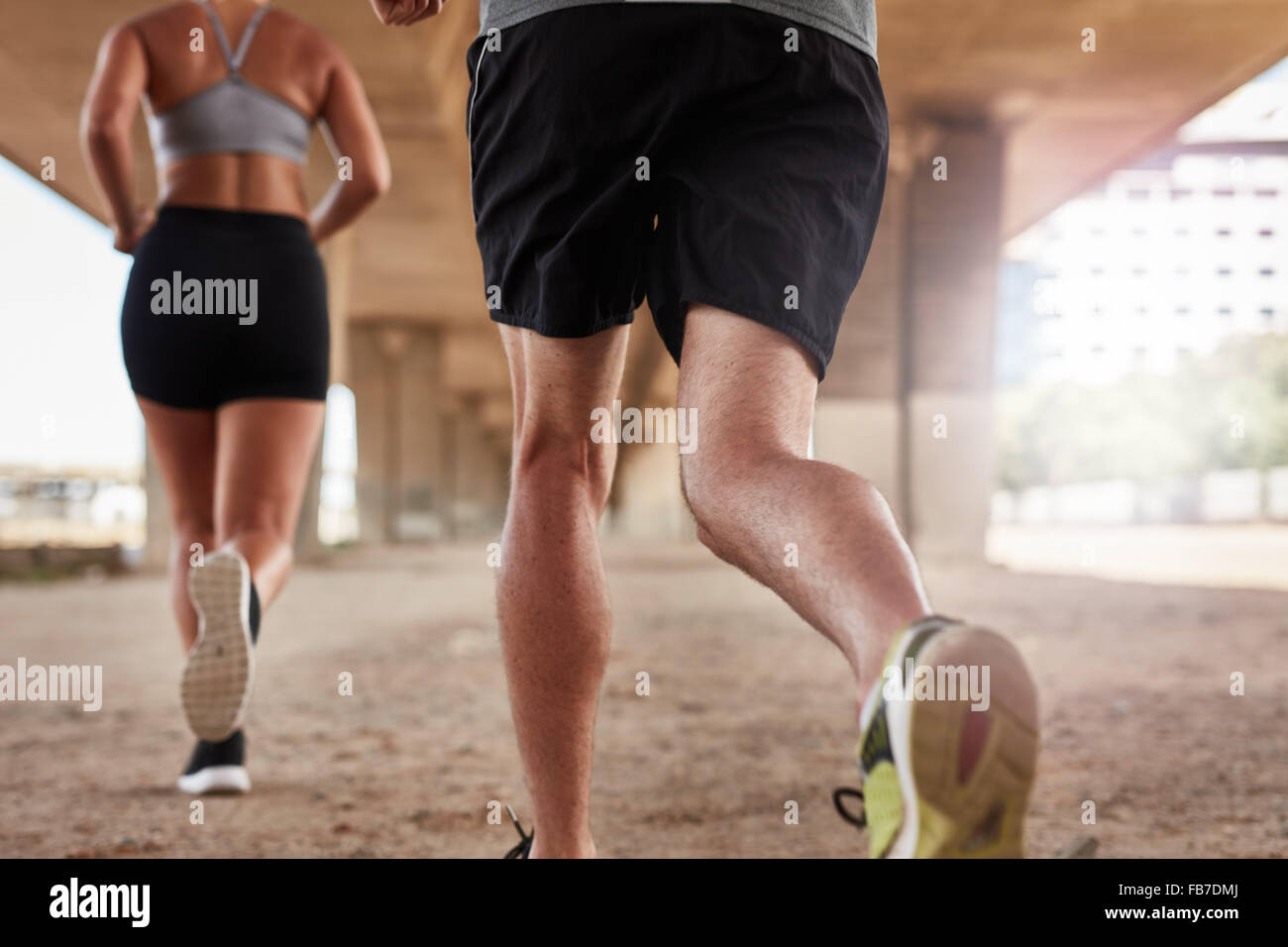 Cropped shot of a two young people running under the bridge in the city. Focus on legs of runners. - Stock Image