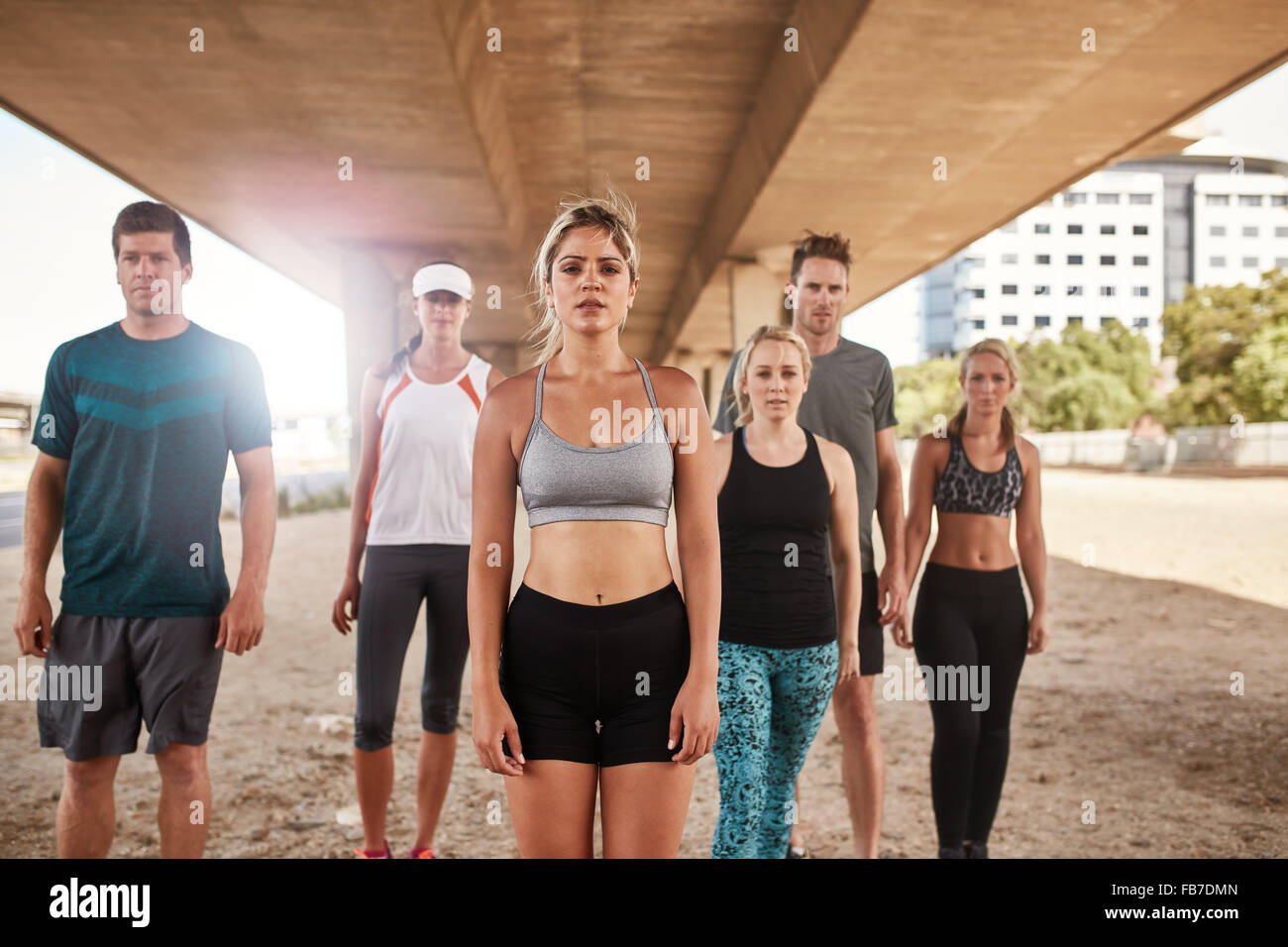 Portrait of running club group standing and looking at camera. Fit young people taking a break after running training. - Stock Image
