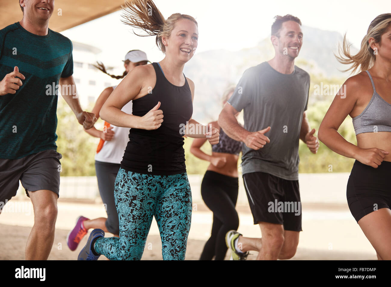 Group of happy young friends running together. Running club members exercising. - Stock Image