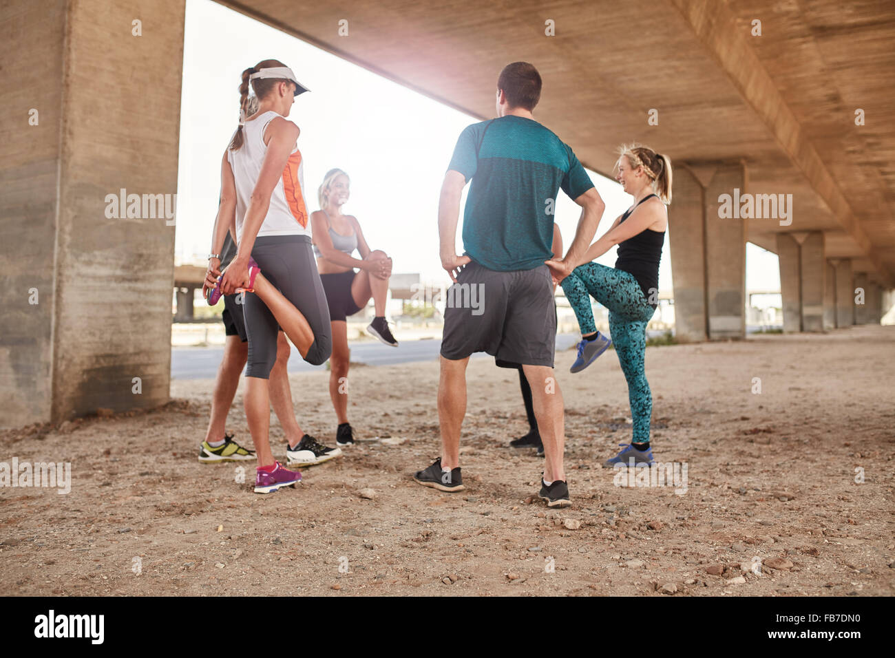 Group of healthy people stretching under a city bridge. Young men and woman taking a break from outdoor training. - Stock Image
