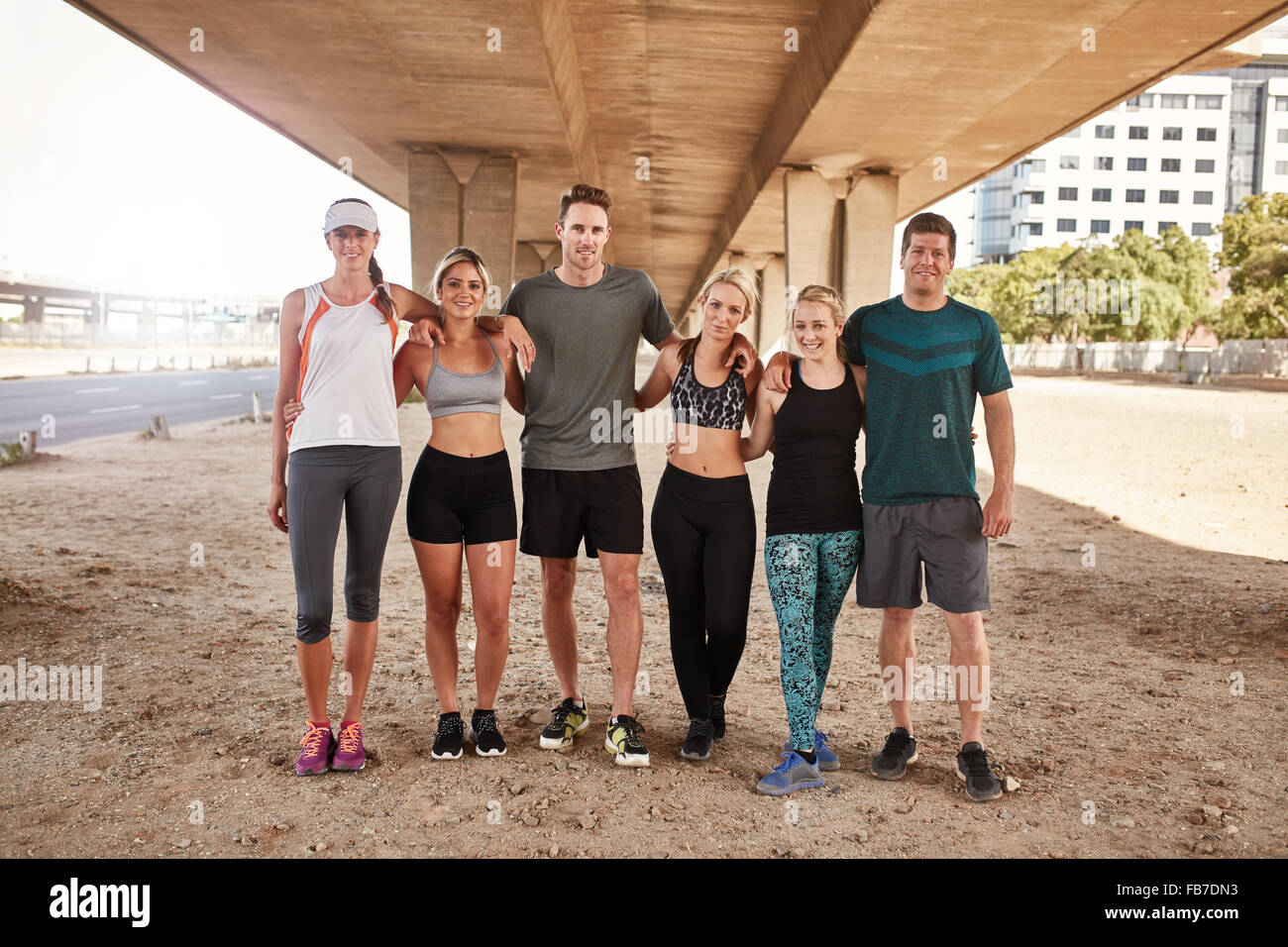 Portrait of running club group standing together and posing for camera. Healthy young men and women training outdoors. - Stock Image