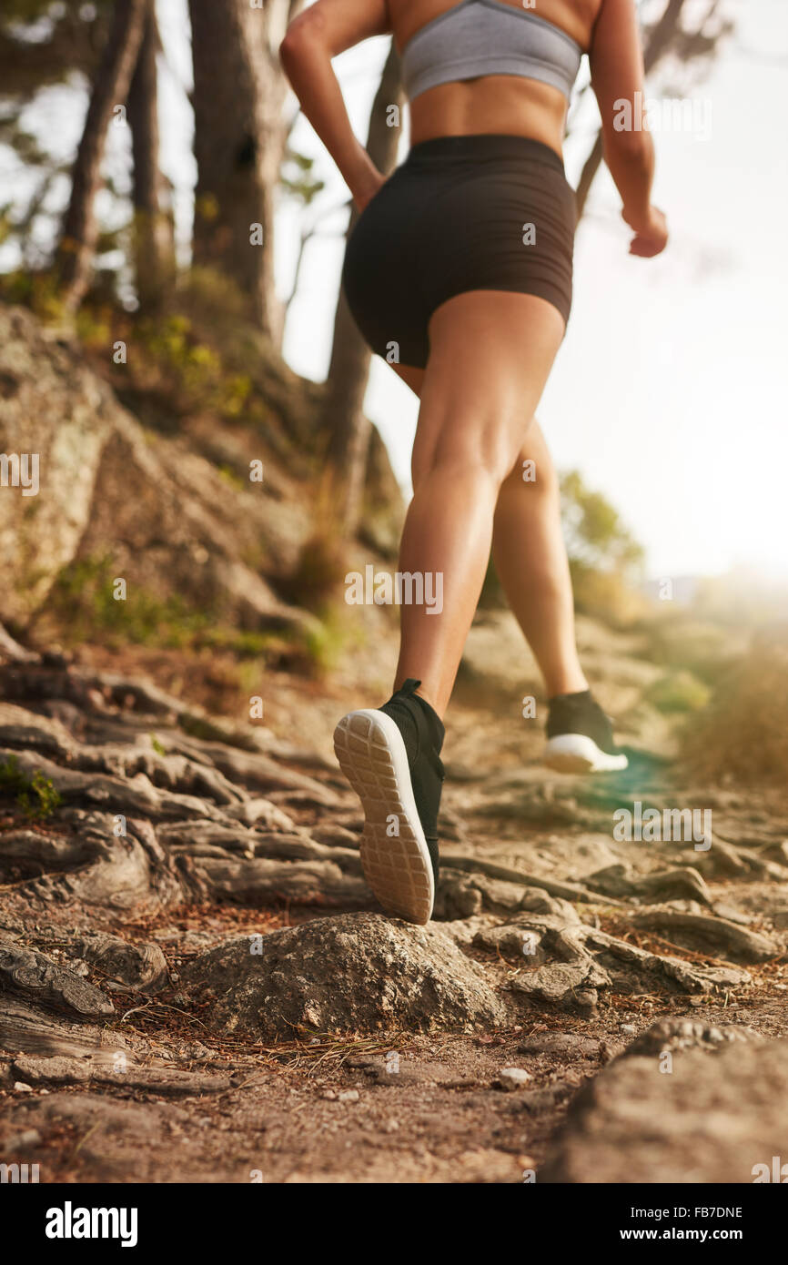 Woman running on rocky trails on the hillside. Rear view image of female runner training outdoors. - Stock Image