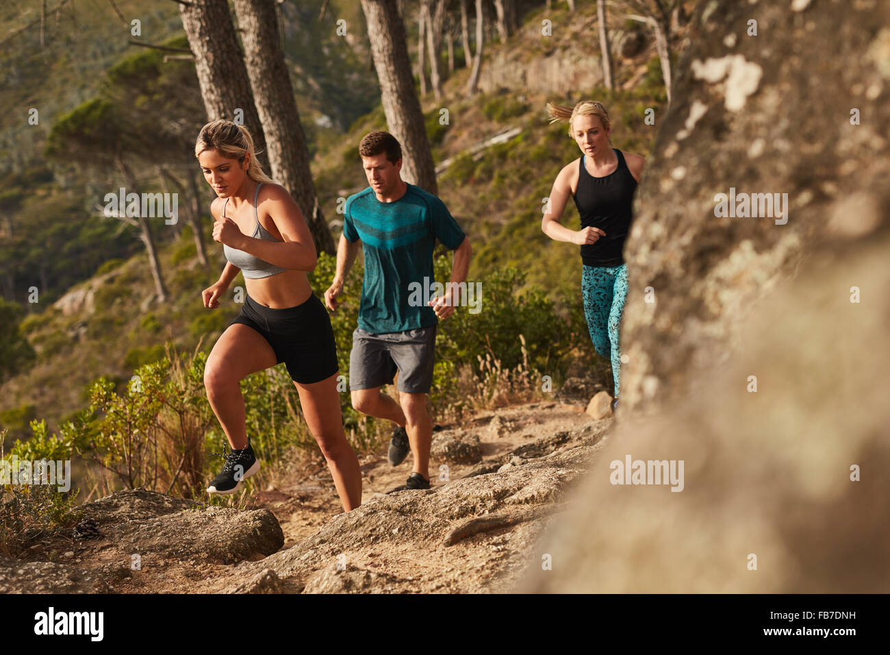 Group of runners running on rocks up a hill. Young people running cross country. - Stock Image