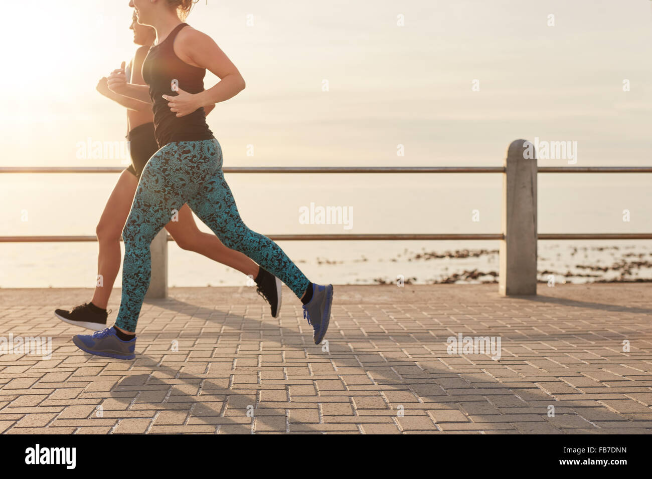 Cropped shot of two young women running along a seaside promenade. Healthy young runners working out together on - Stock Image