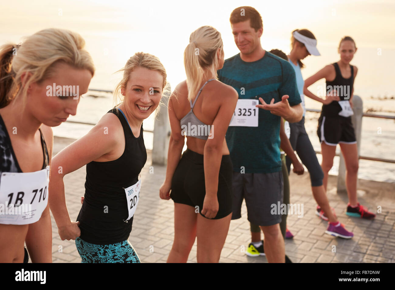 Group of happy young athletes standing on starting line and talking before start of the race. Running club group - Stock Image