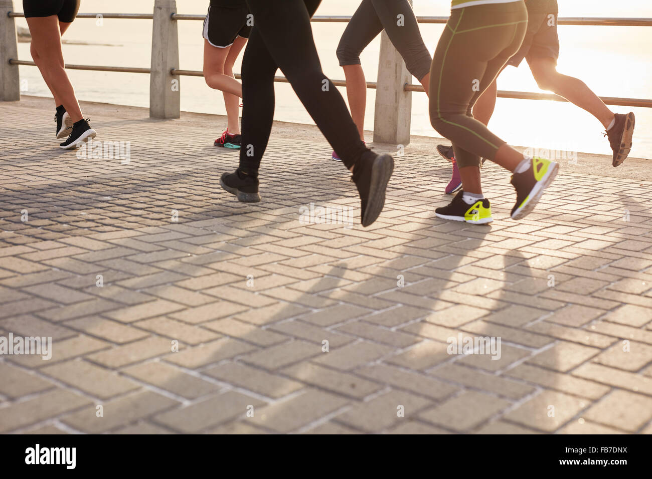 Legs of runners training together on seaside promenade. People running on the street by the sea. - Stock Image