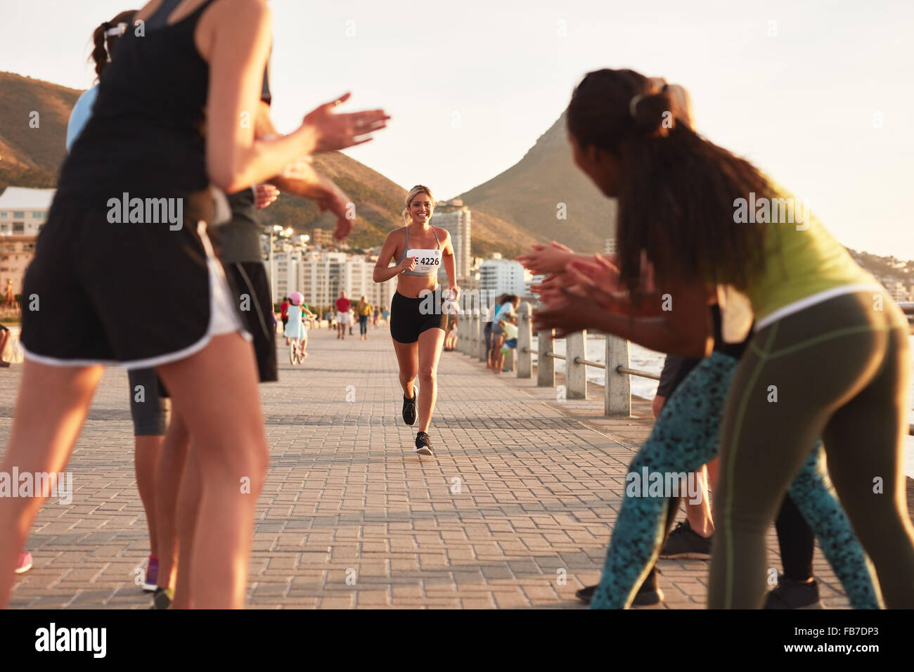 Happy young female athlete being applauded by supporters as she reaches the finishing line of a running race. Young - Stock Image