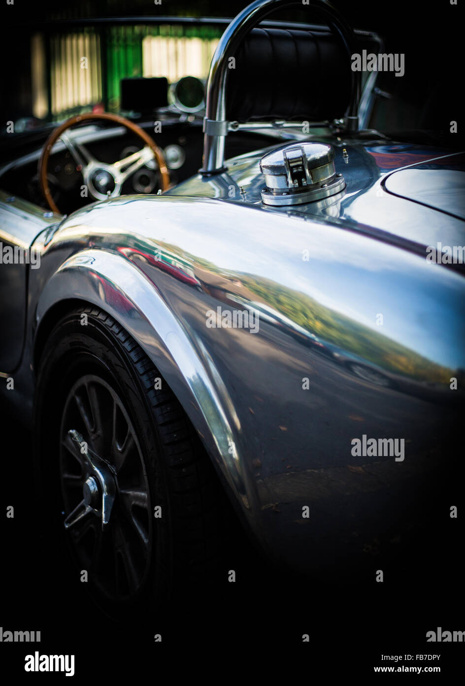 aluminum body convertible AC Cobra rear drivers side view showing fuel cap and steering wheel - Stock Image