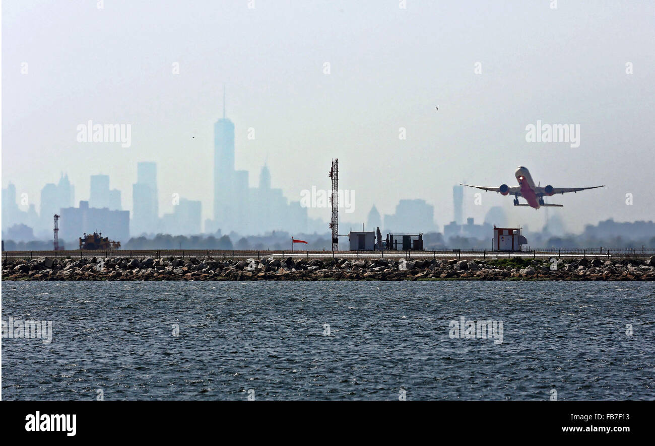 An aircraft takes off from JFK Airport against a backdrop of the hazy New York Skyline. - Stock Image