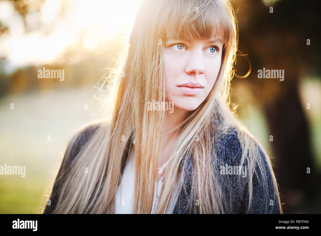 Troubled young woman looking off into the distance with the sun at her back - Stock Image