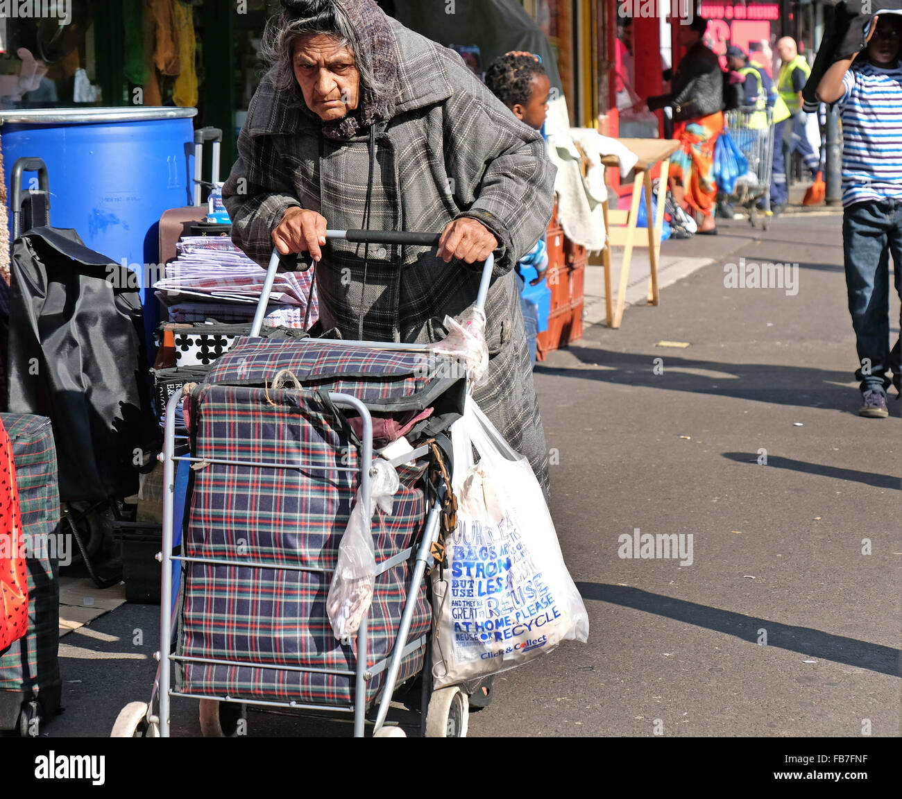 An elderly woman with a trolley shopping in streets of Brixton South London - Stock Image