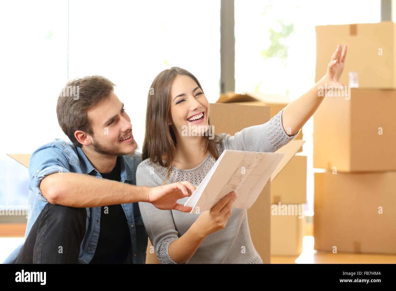 Happy couple planning decoration when moving home sitting on the floor - Stock Image