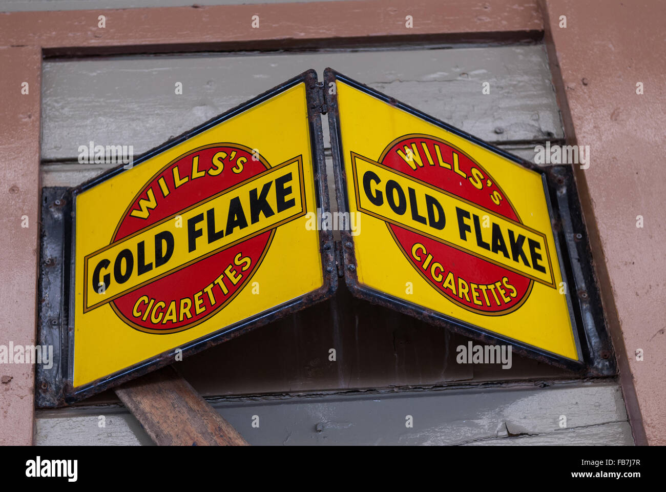 Vintage enameled advertising plaque mounted on timber boards. Advertising Will's Gold Flake cigarettes - Stock Image