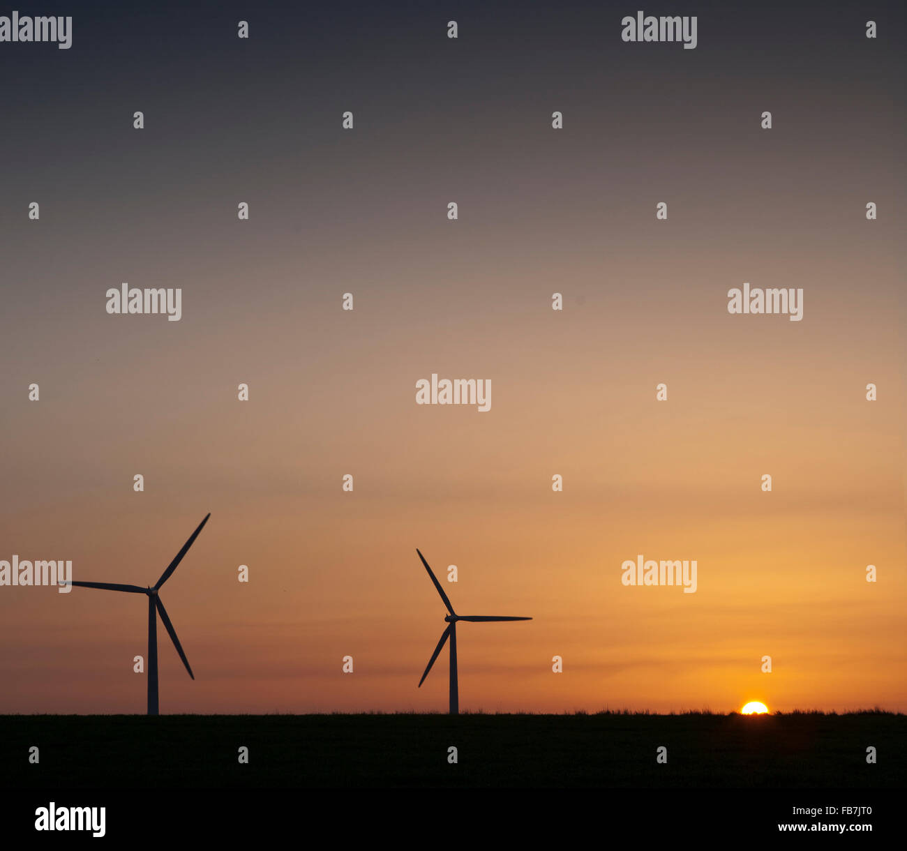 Sun rise over wind turbines in a Wiltshire field - Stock Image