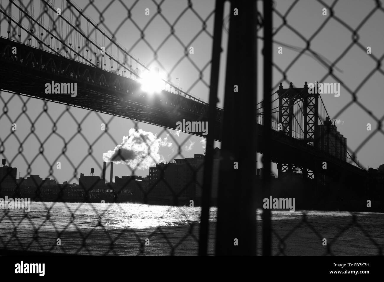 Distorted industrial view of Manhattan Bridge waterfront New York City through a wire safety fence. Monochrome, - Stock Image