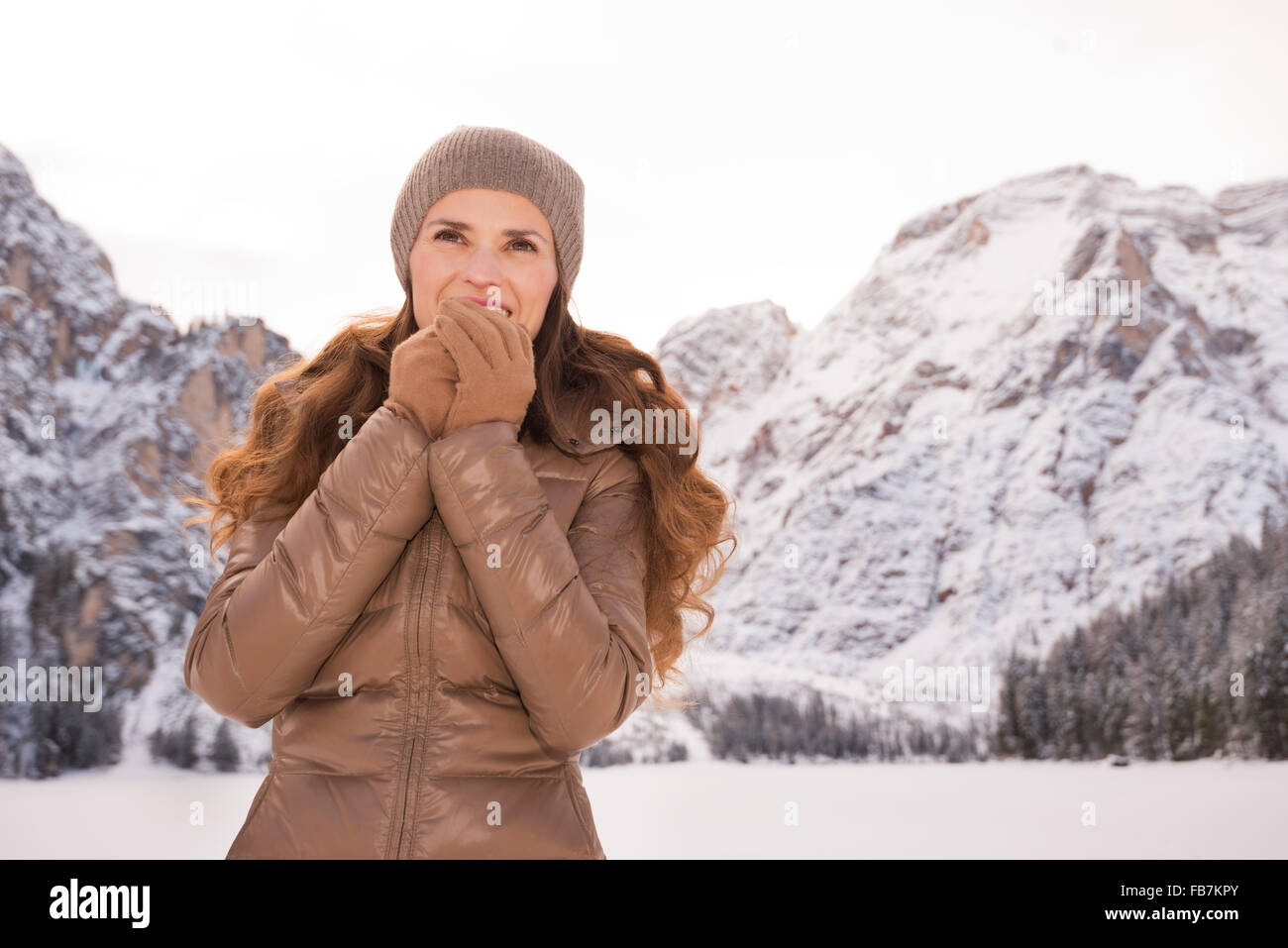 Energy-filling and exciting winter weekends in the mountains. Portrait of smiling young woman warming hands with - Stock Image