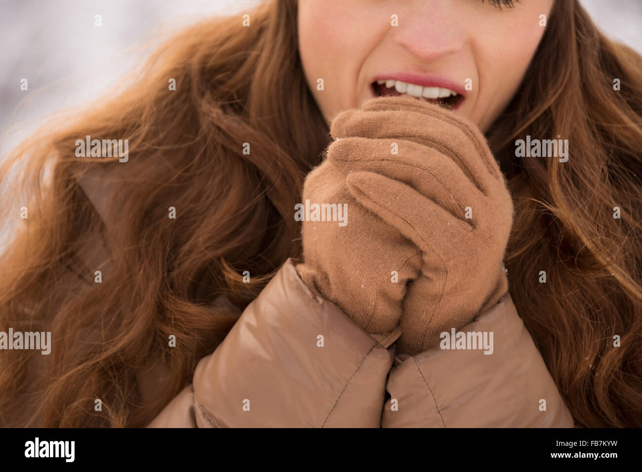 Energy-filling and exciting winter weekends in the mountains. Closeup on woman warming hands with breathe outdoors - Stock Image