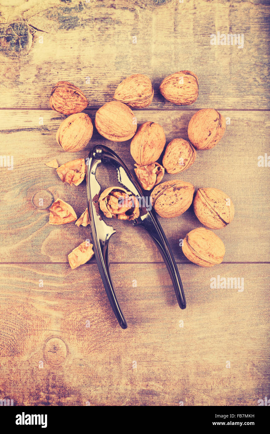 Vintage stylized walnuts and nutcracker on wooden background, space for text. - Stock Image