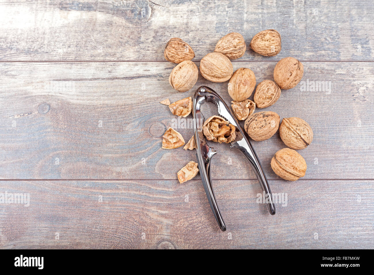 Walnuts and nutcracker on wooden background, space for text. - Stock Image